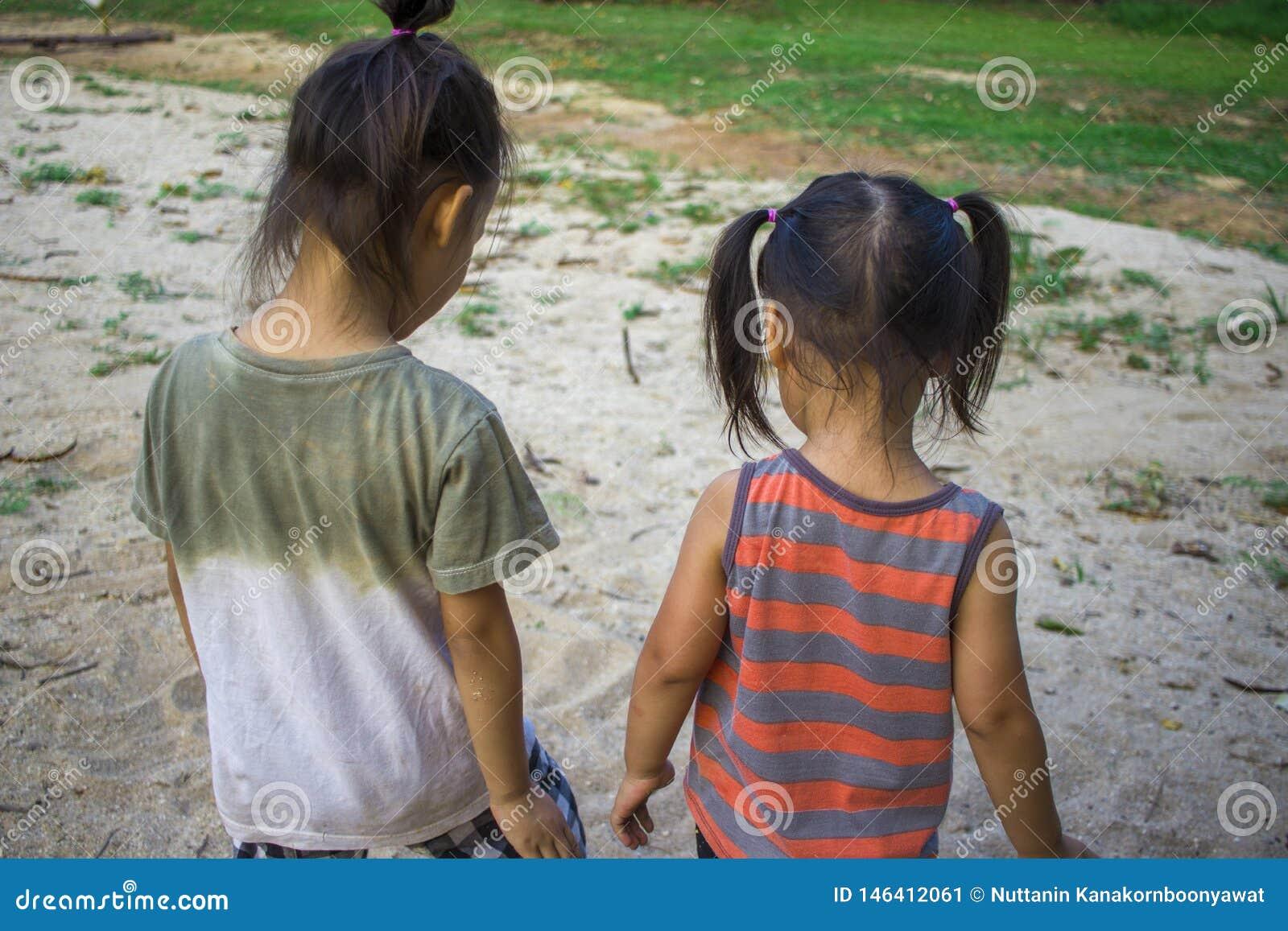 Bambino felice che gioca con la sabbia, famiglia asiatica divertente in un parco
