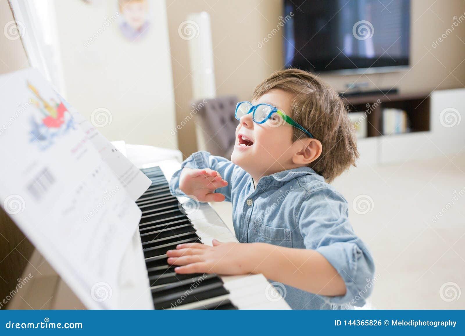 Bambino felice che gioca piano