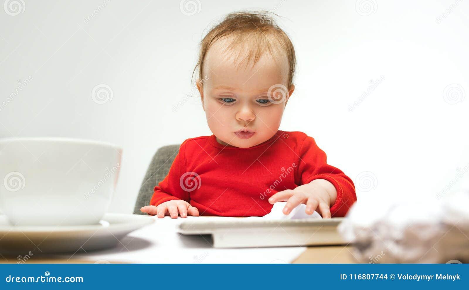 Bambino felice della neonata del bambino che si siede con la tastiera del computer su un fondo bianco