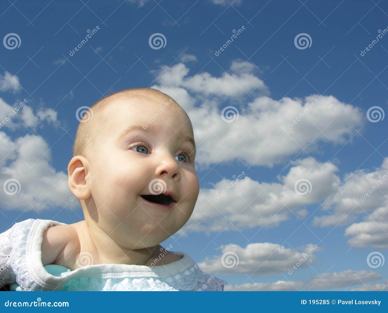 Bambino felice sotto le nubi