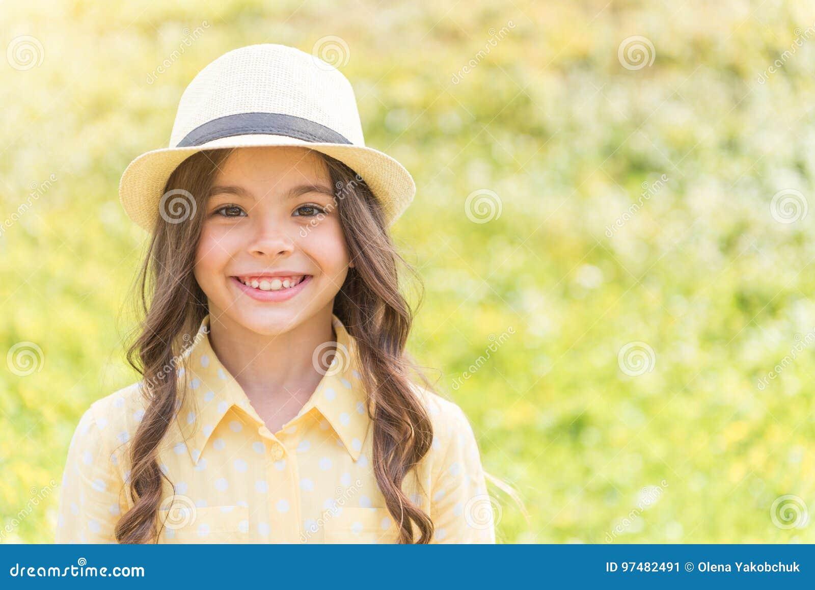 Bambino femminile allegro che gode della natura sul pascolo