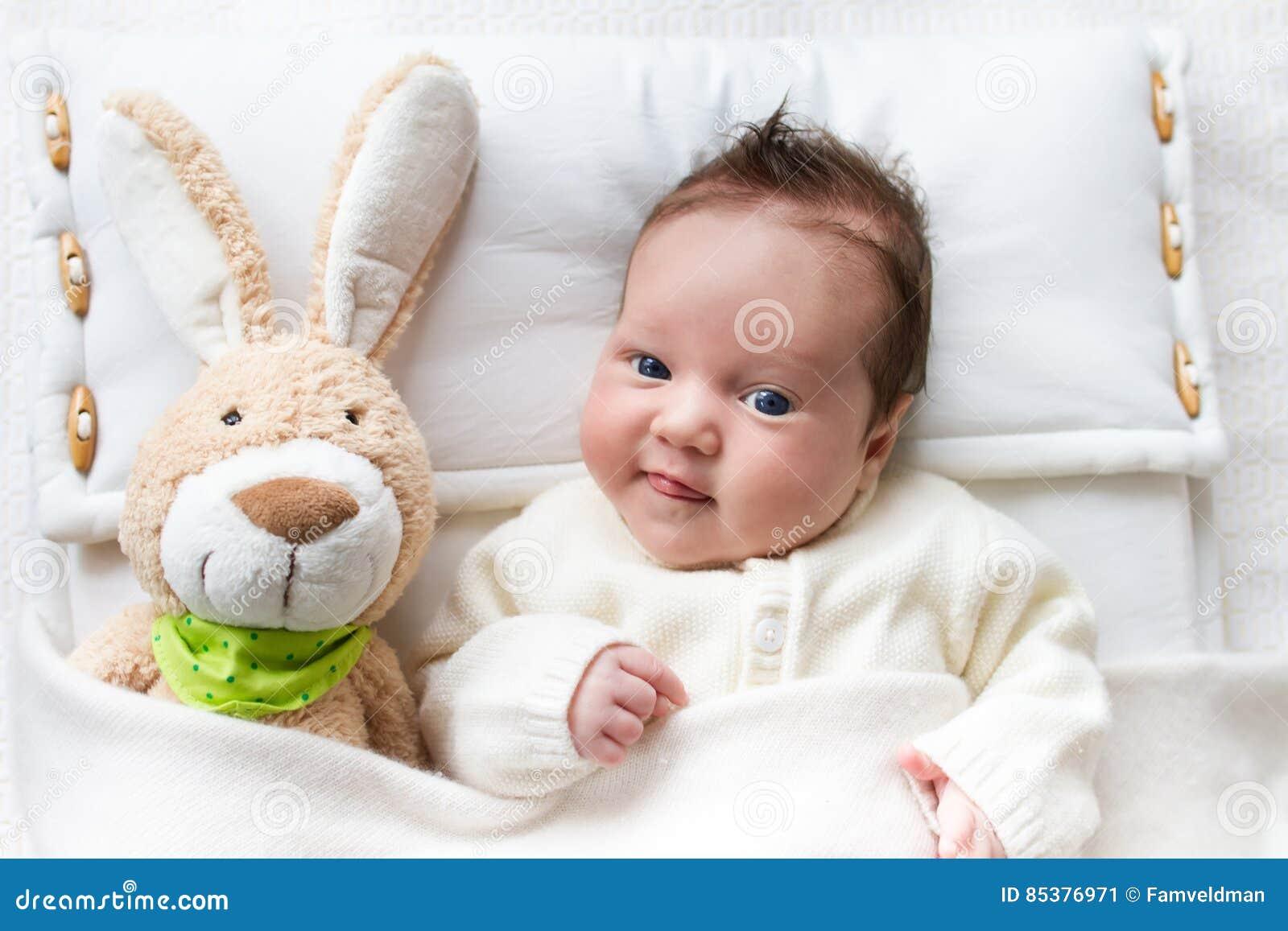 Bambino a letto con il giocattolo del coniglietto