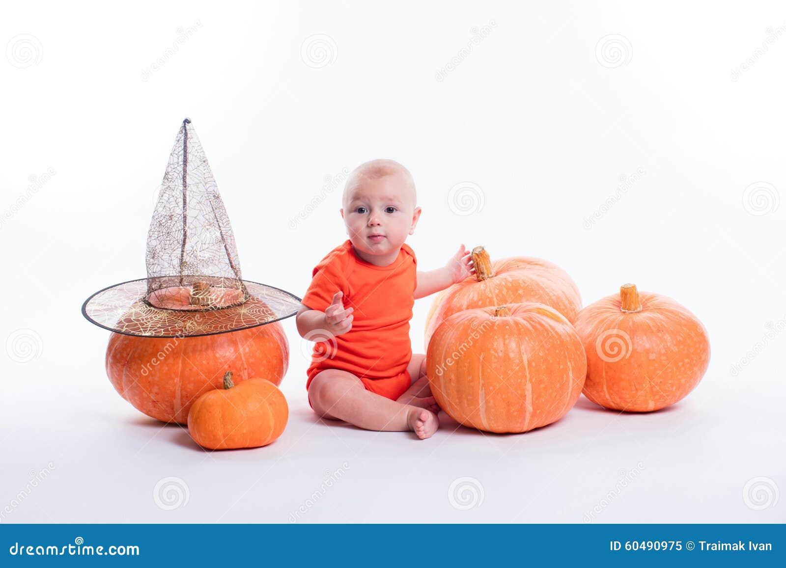 Bambino in maglietta arancio che si siede su un fondo bianco circondato