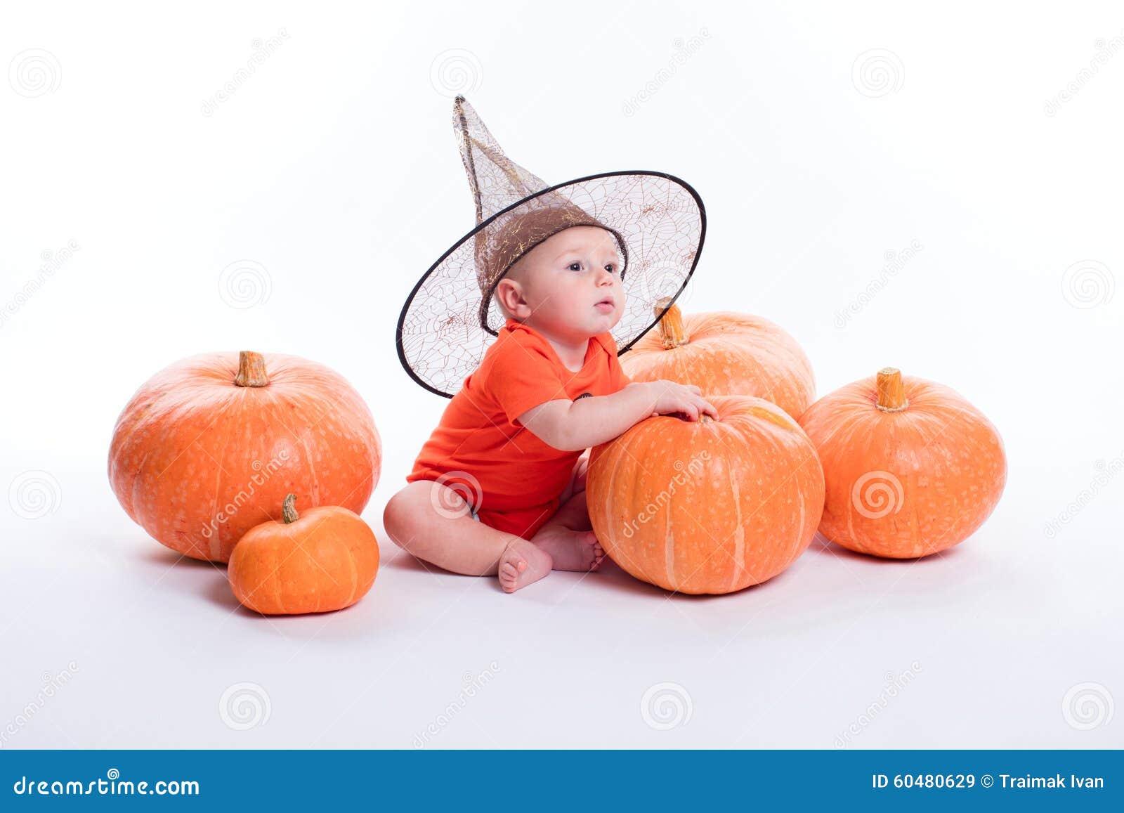 Bambino in maglietta arancio su un fondo bianco che si siede in un witche