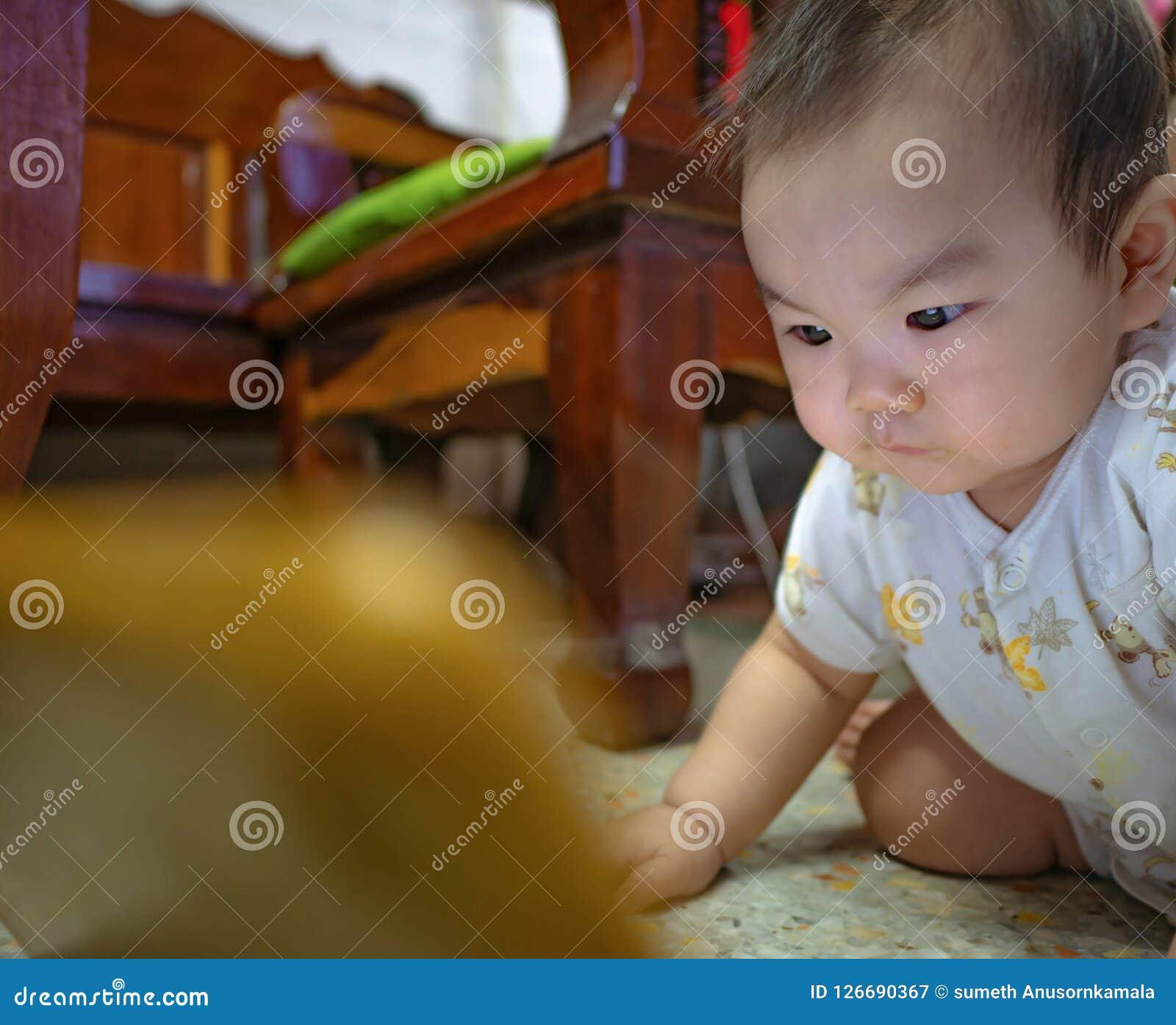 Bambino maschio asiatico di Cutie molto serio e sguardo alla compressa