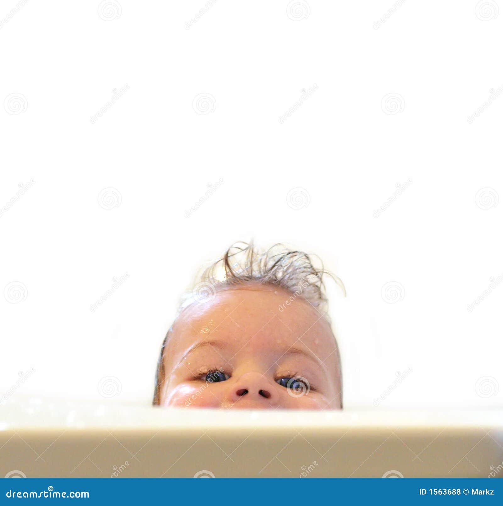 Bambino eyed blu che ride e che sembra divertente sopra il bordo di un ...