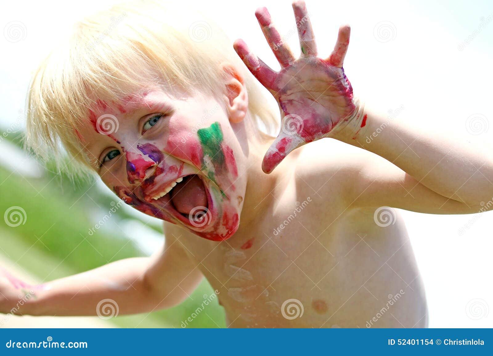 Bambino piccolo felice con il fronte dipinto sudicio