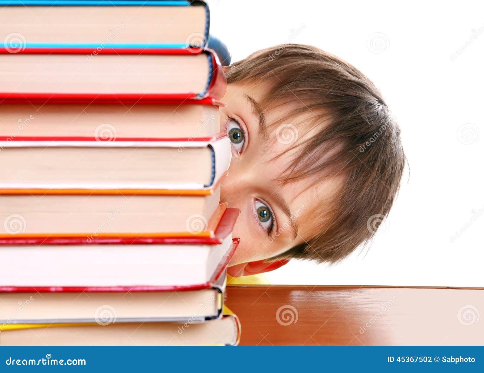Bambino sorpreso dietro i libri