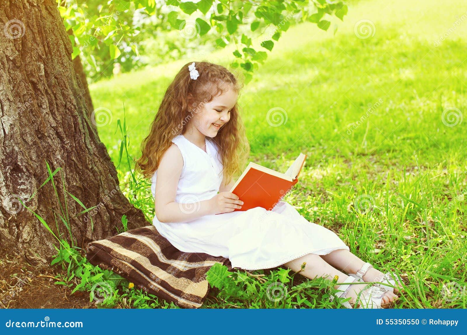 Bambino sorridente della bambina che legge un libro sull erba vicino all albero