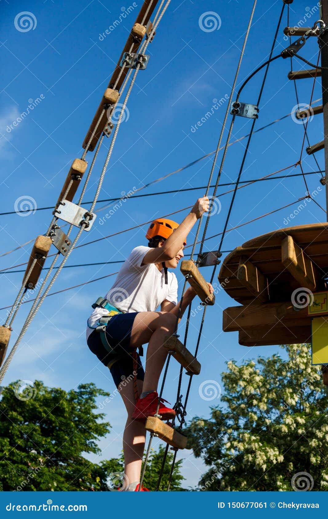 Bambino sportivo attivo in casco che fa attività nel parco di avventura con tutta l attrezzatura rampicante I bambini attivi scal