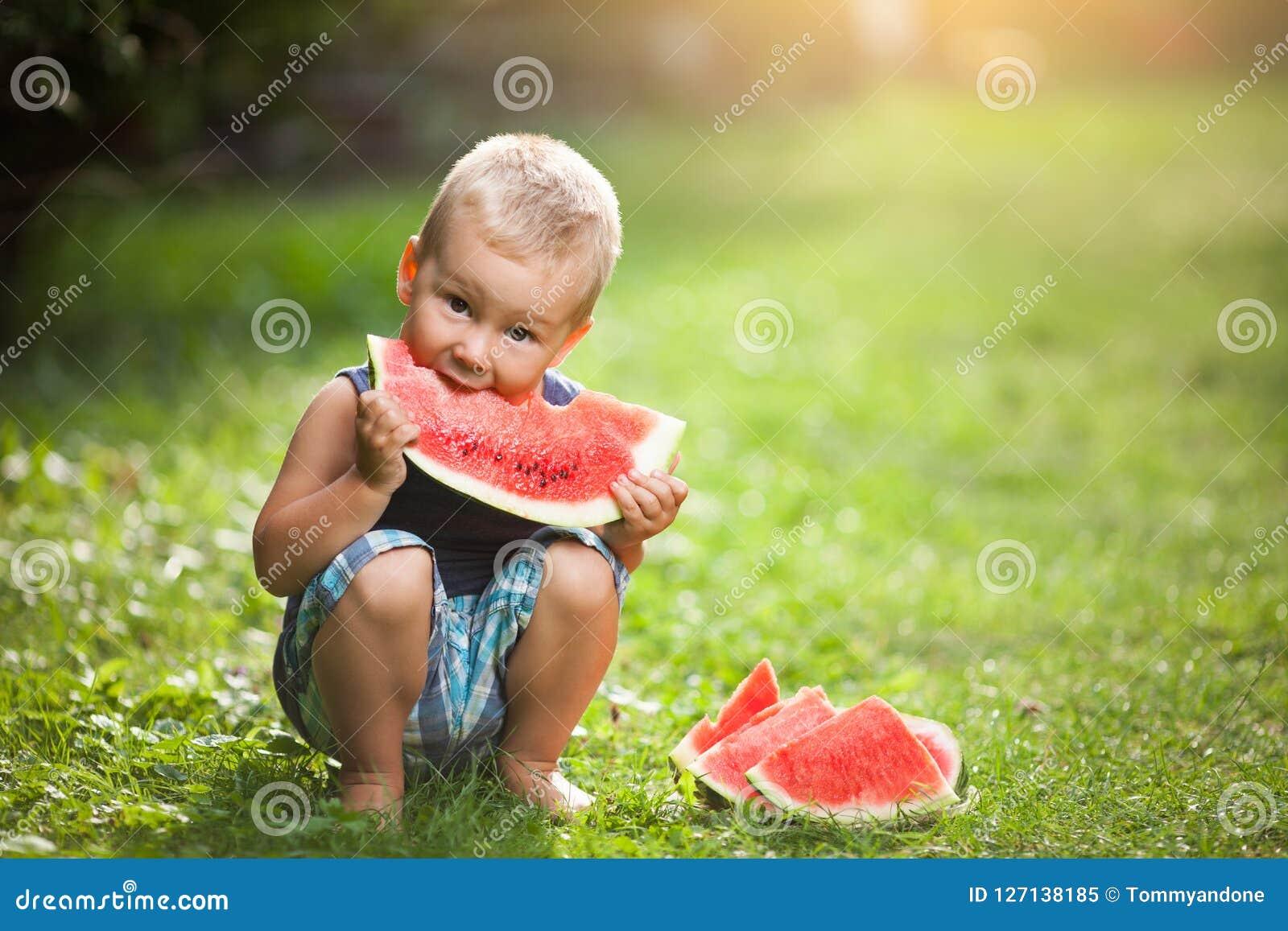 Bambino sveglio che mangia una fetta di anguria
