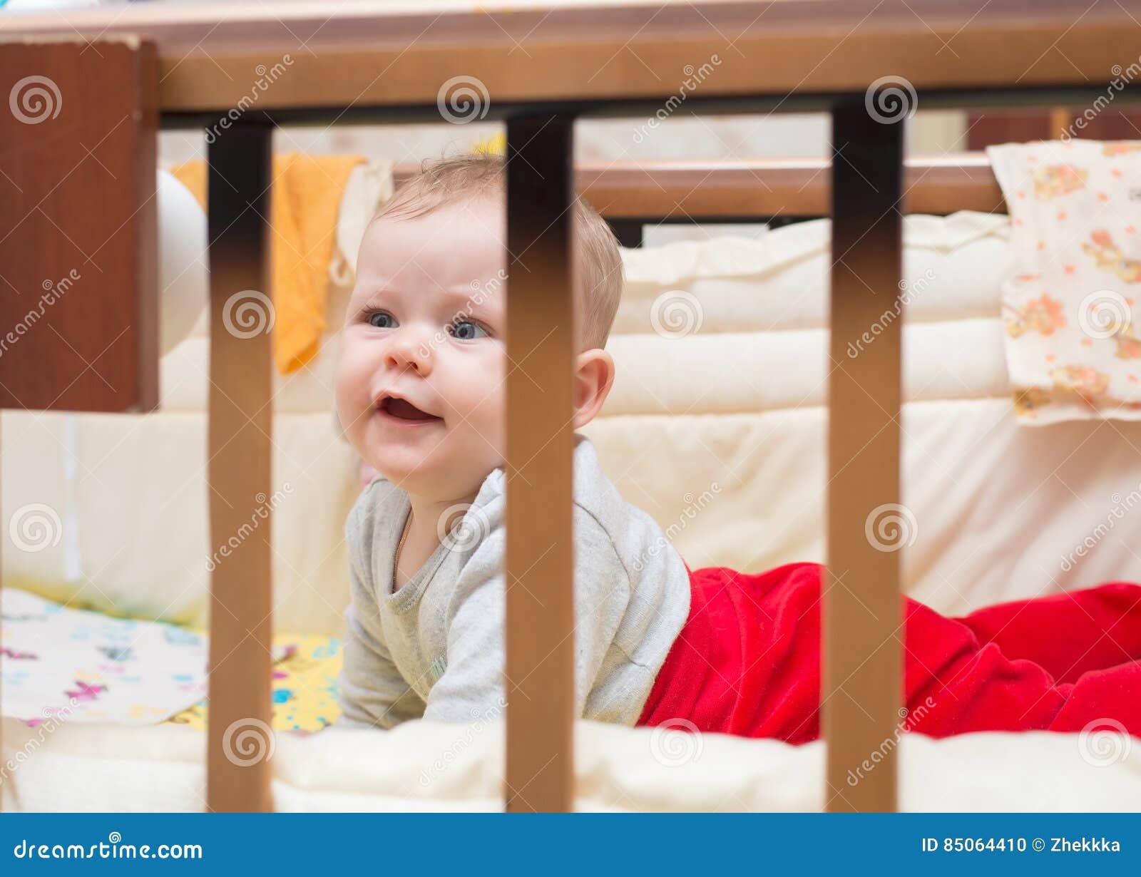 Bambino sveglio che si trova sul suo stomaco nel suo letto fotografia stock immagine 85064410 - Letto che si chiude ...