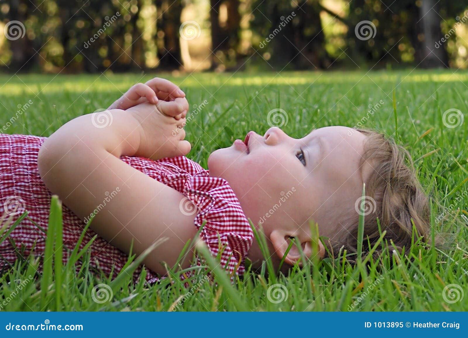 Bambino sveglio che si trova sull erba