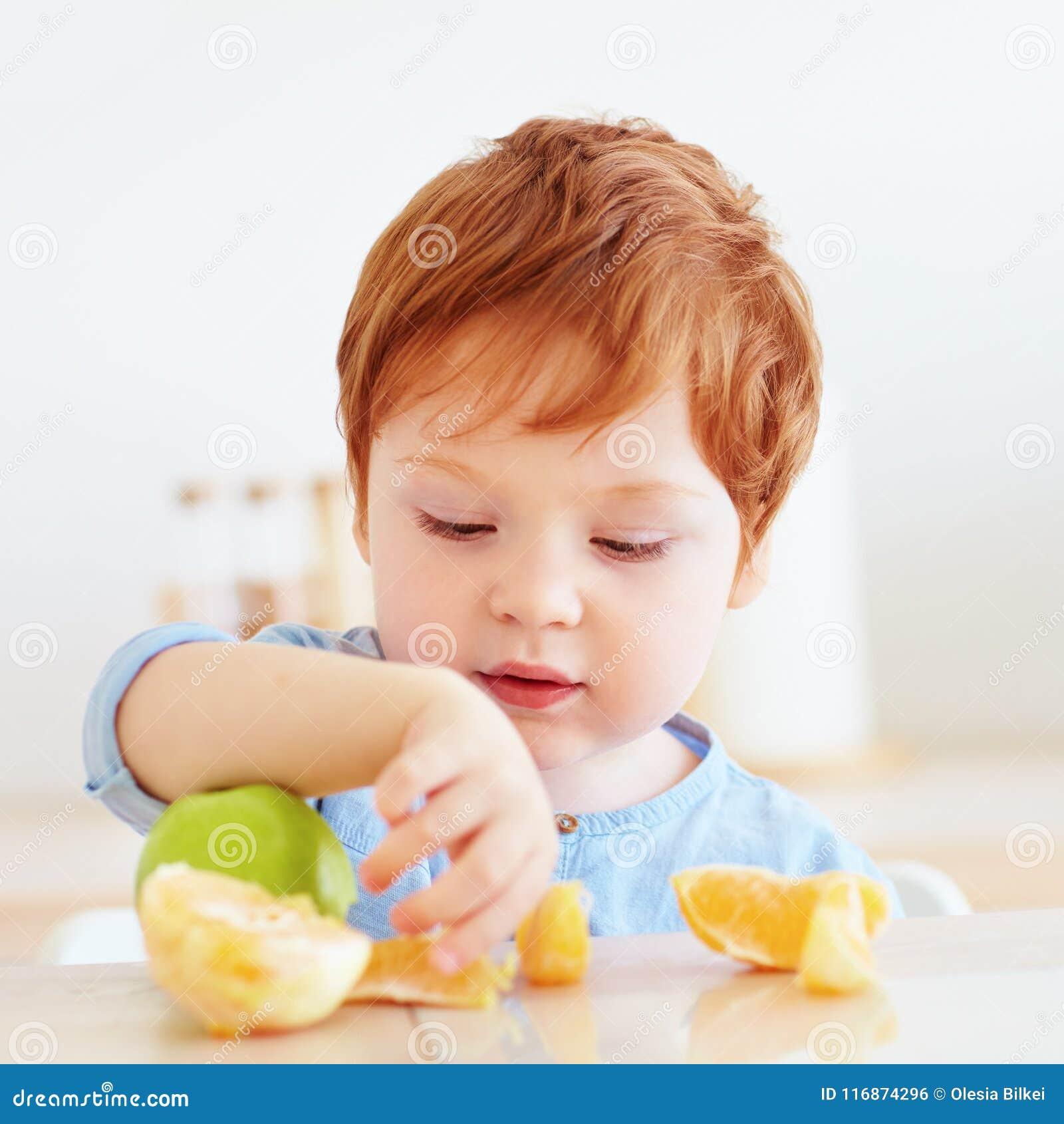 Bambino sveglio del bambino della testarossa che prova frutti dell arancia e della mela fresca