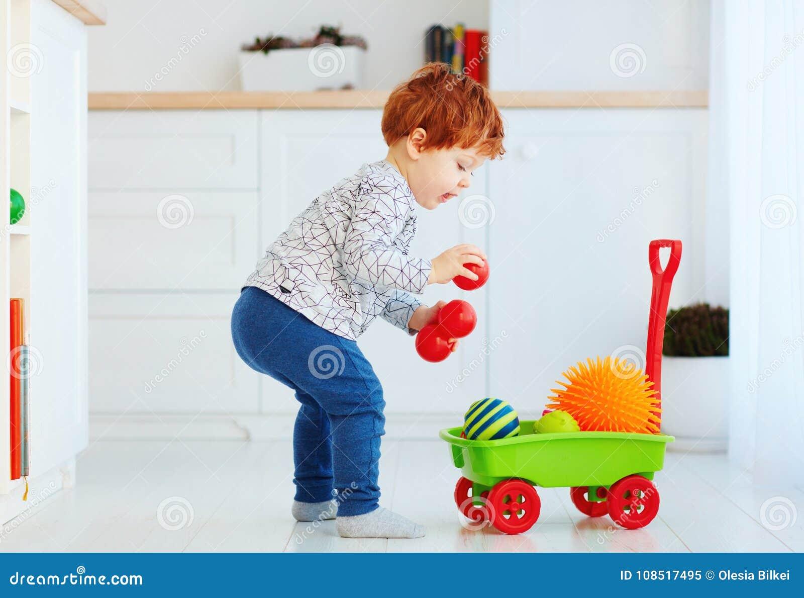 Bambino sveglio del bambino della testarossa che raccoglie le palle differenti nel carretto a mano del giocattolo