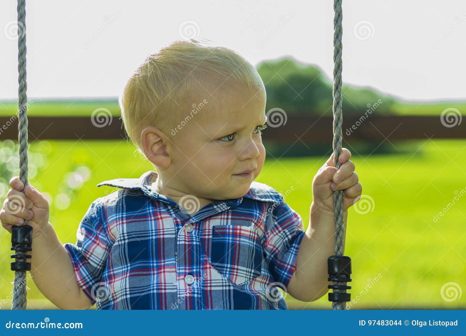 Bambino sveglio su un oscillazione all aperto Ritratto del neonato adorabile che gioca su un campo da giuoco del bambino
