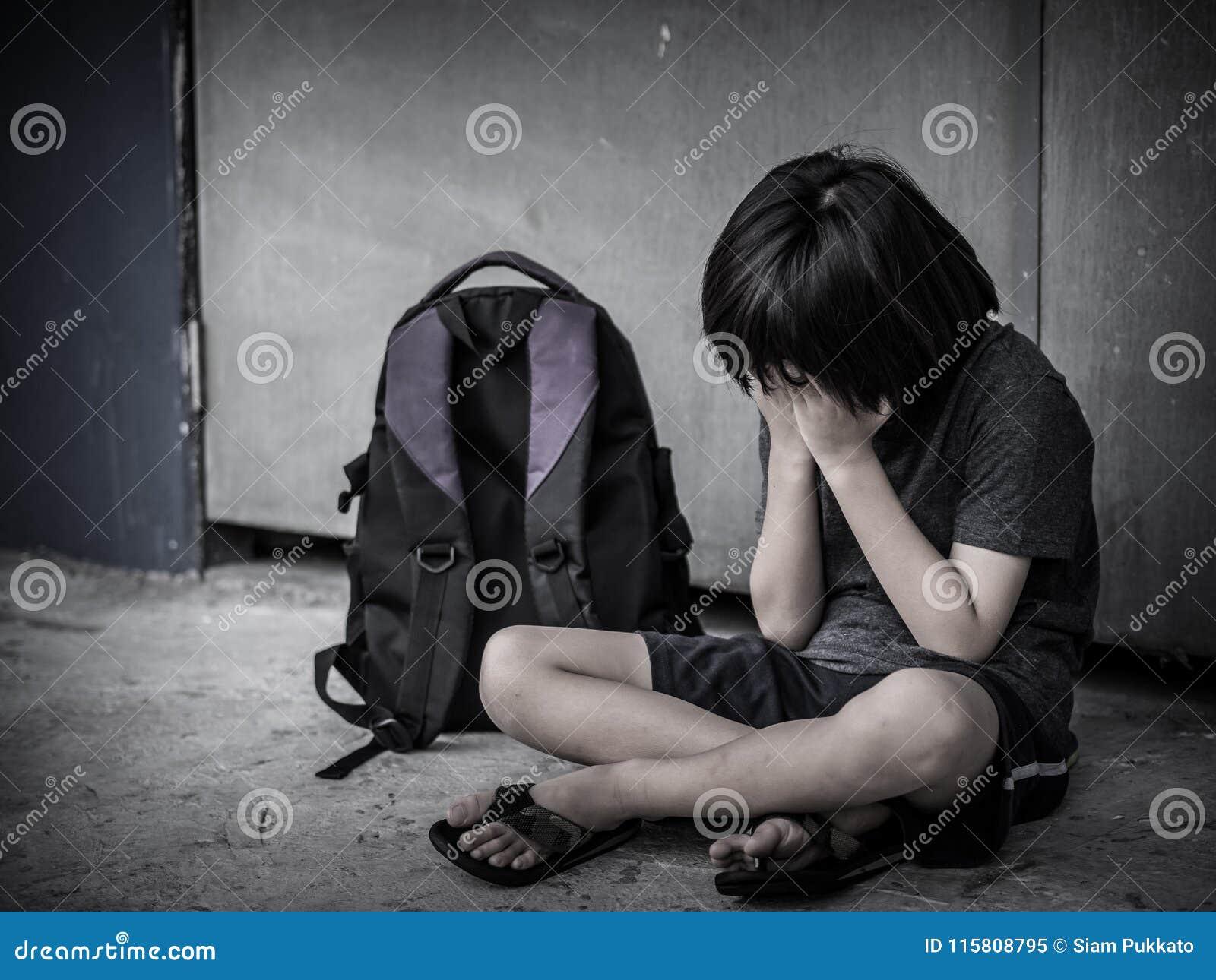 Bambino triste che si siede sul pavimento con il genitore aspettante della borsa di scuola