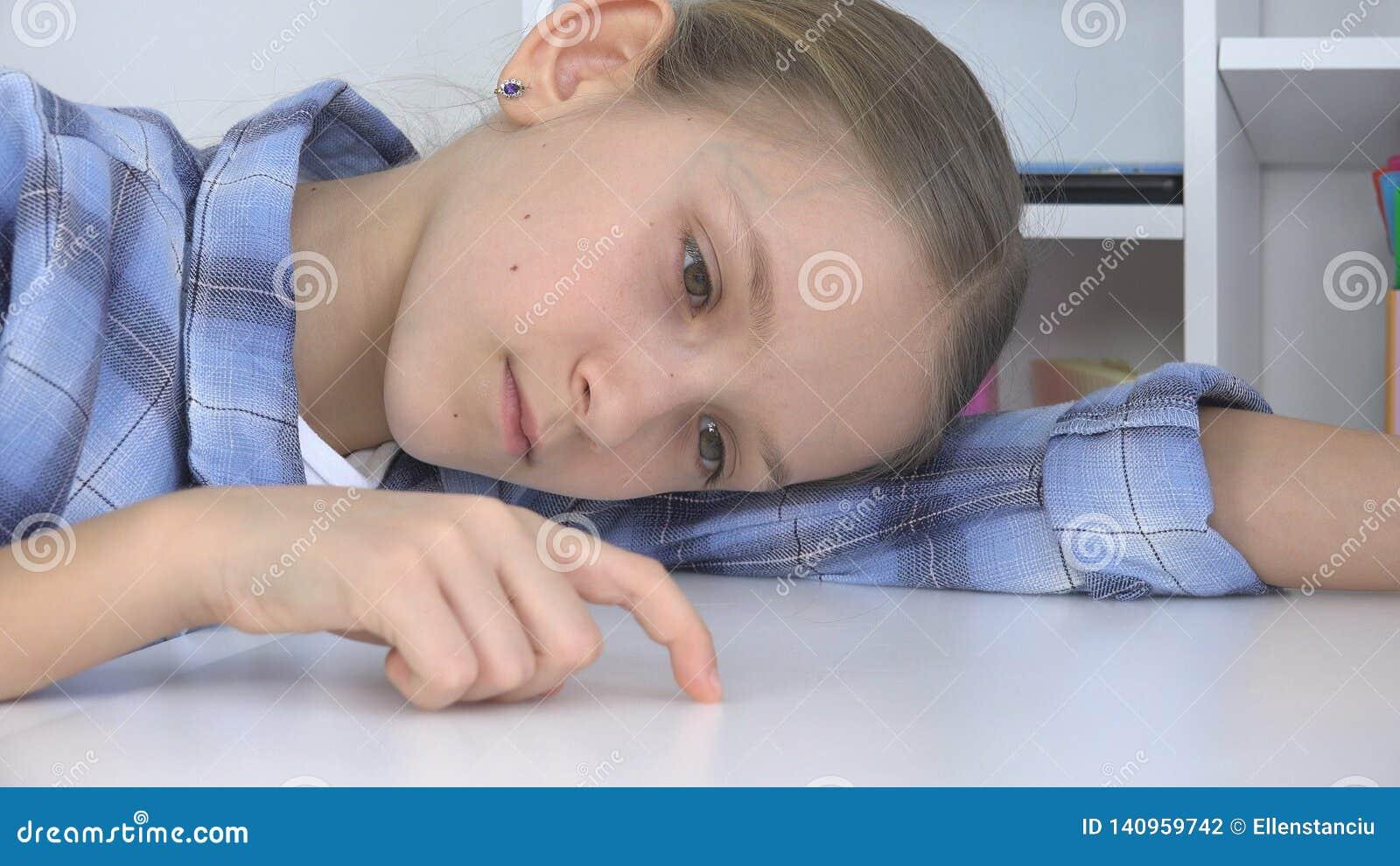 Bambino triste, ragazza annoiata che gioca le dita sullo scrittorio, bambino infelice sollecitato che non studia