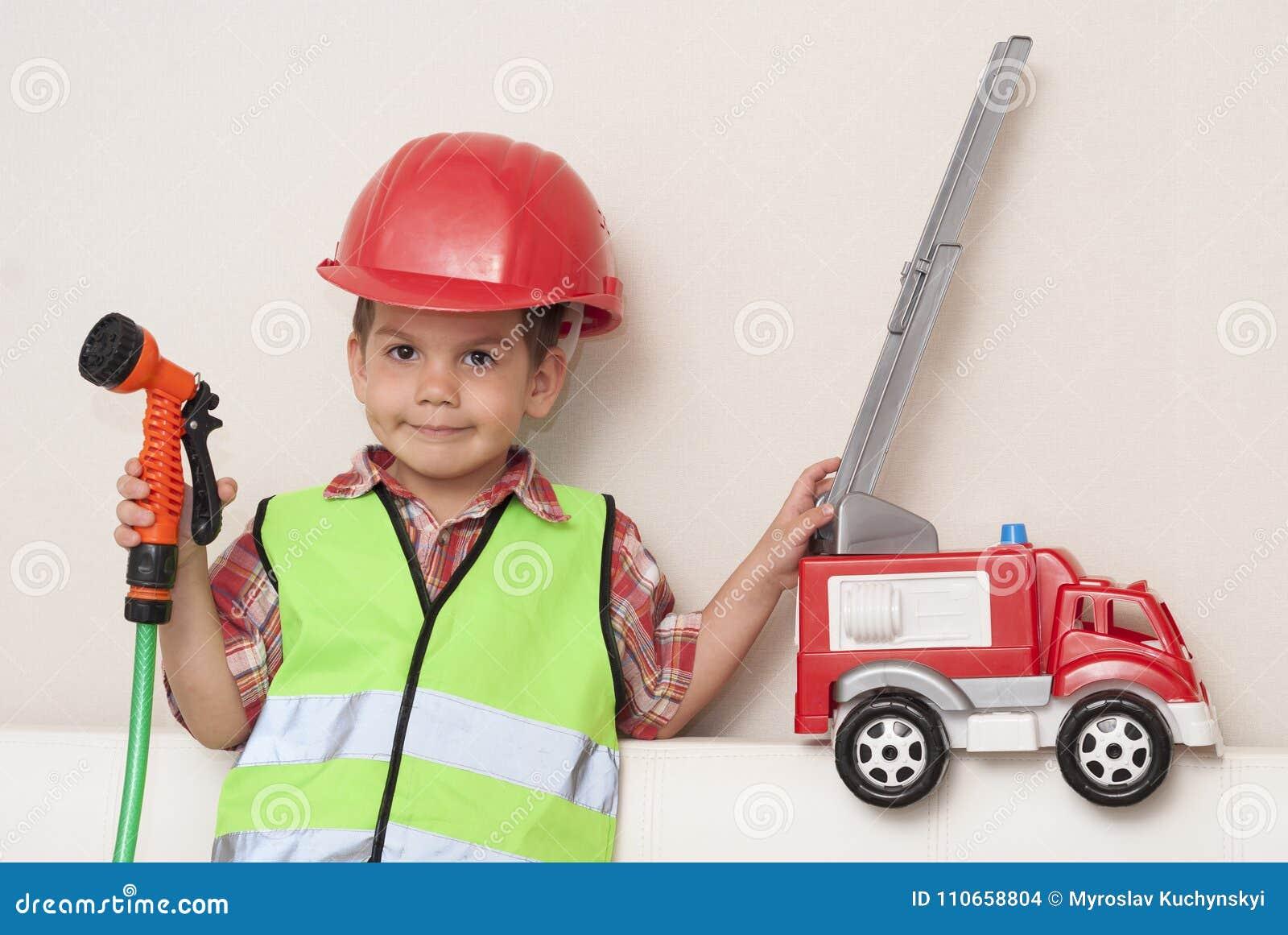 Bambino in un casco rosso e con un autopompa antincendio