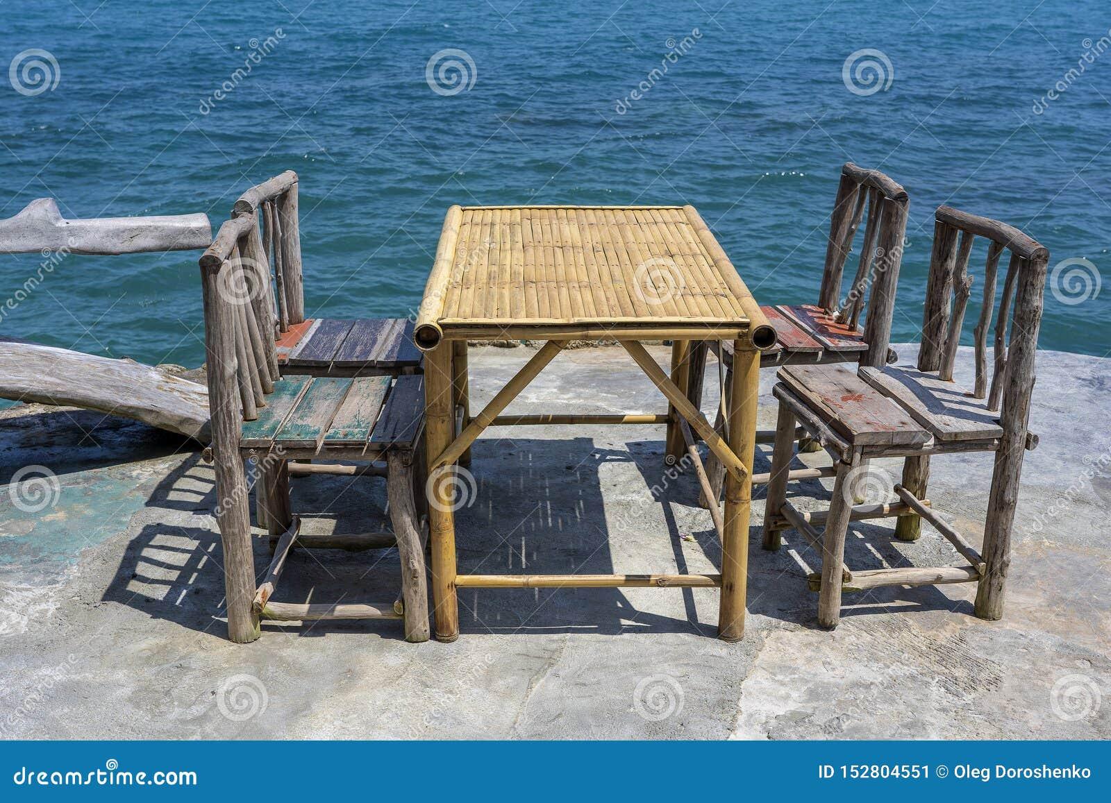 Bamboelijst en houten stoelen in lege koffie naast zeewater in tropisch strand Eiland Koh Phangan, Thailand