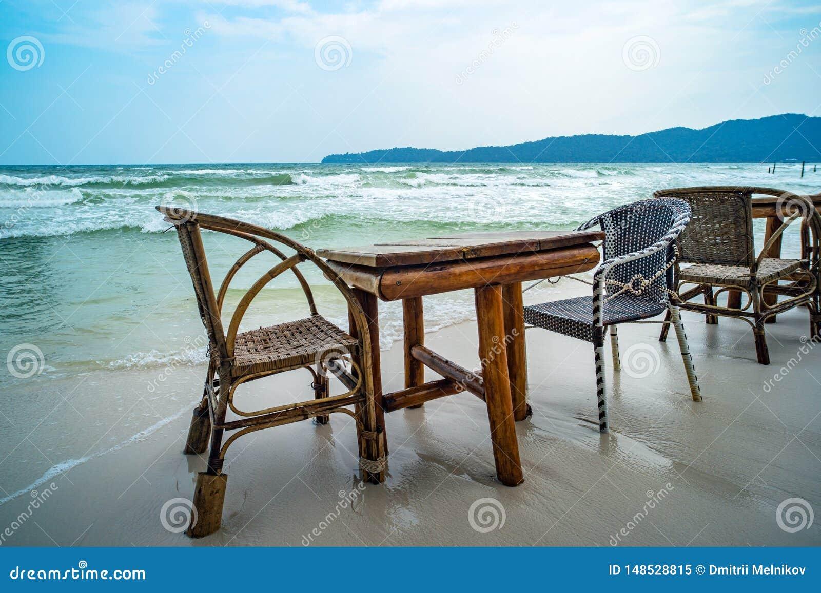Bamboelijst en houten stoelen in lege koffie naast zeewater in tropisch strand Sluit omhoog Eiland Koh Phangan