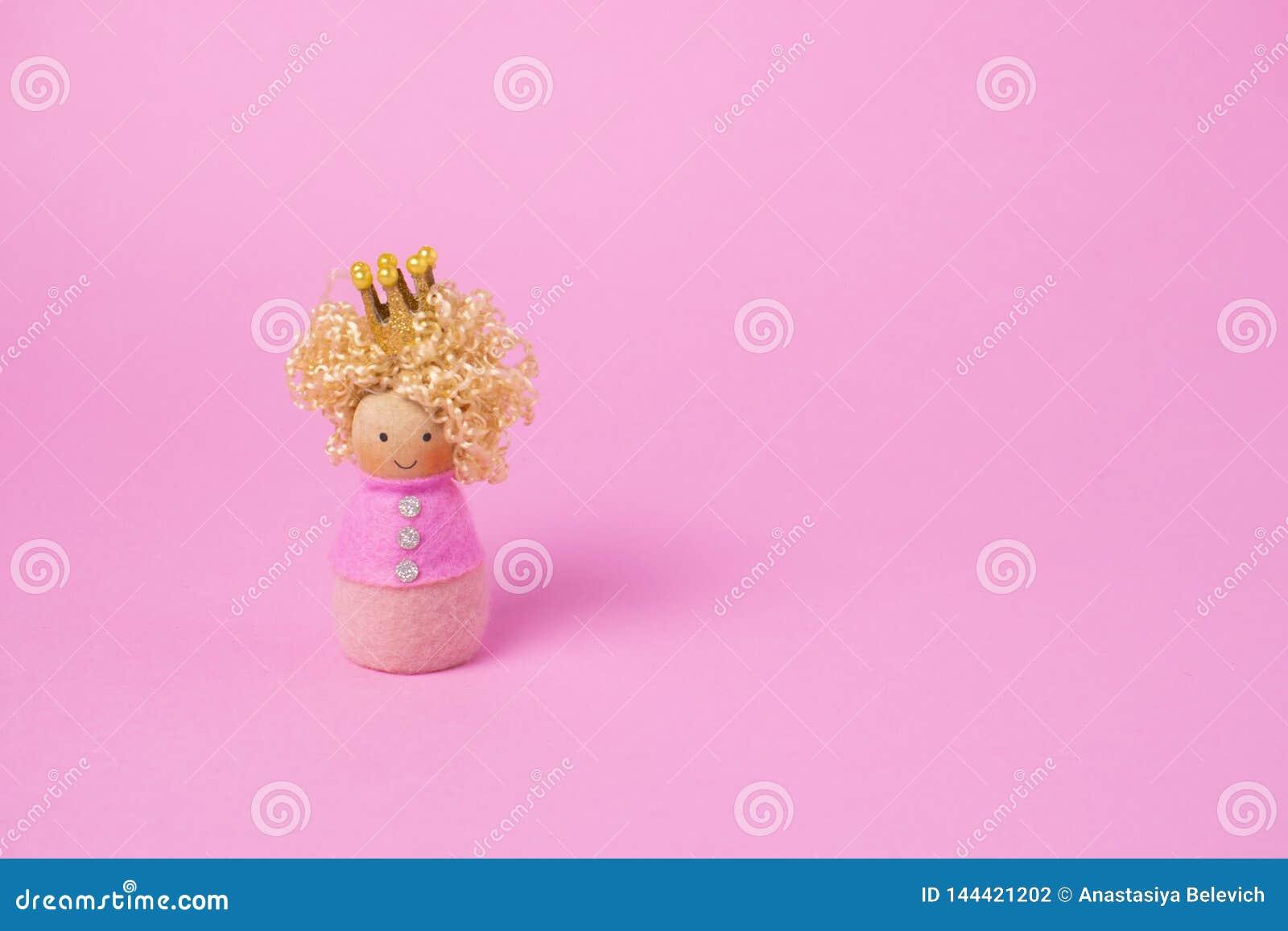 Bambola di legno di principessa su fondo rosa Concetto minimo Copi lo spazio