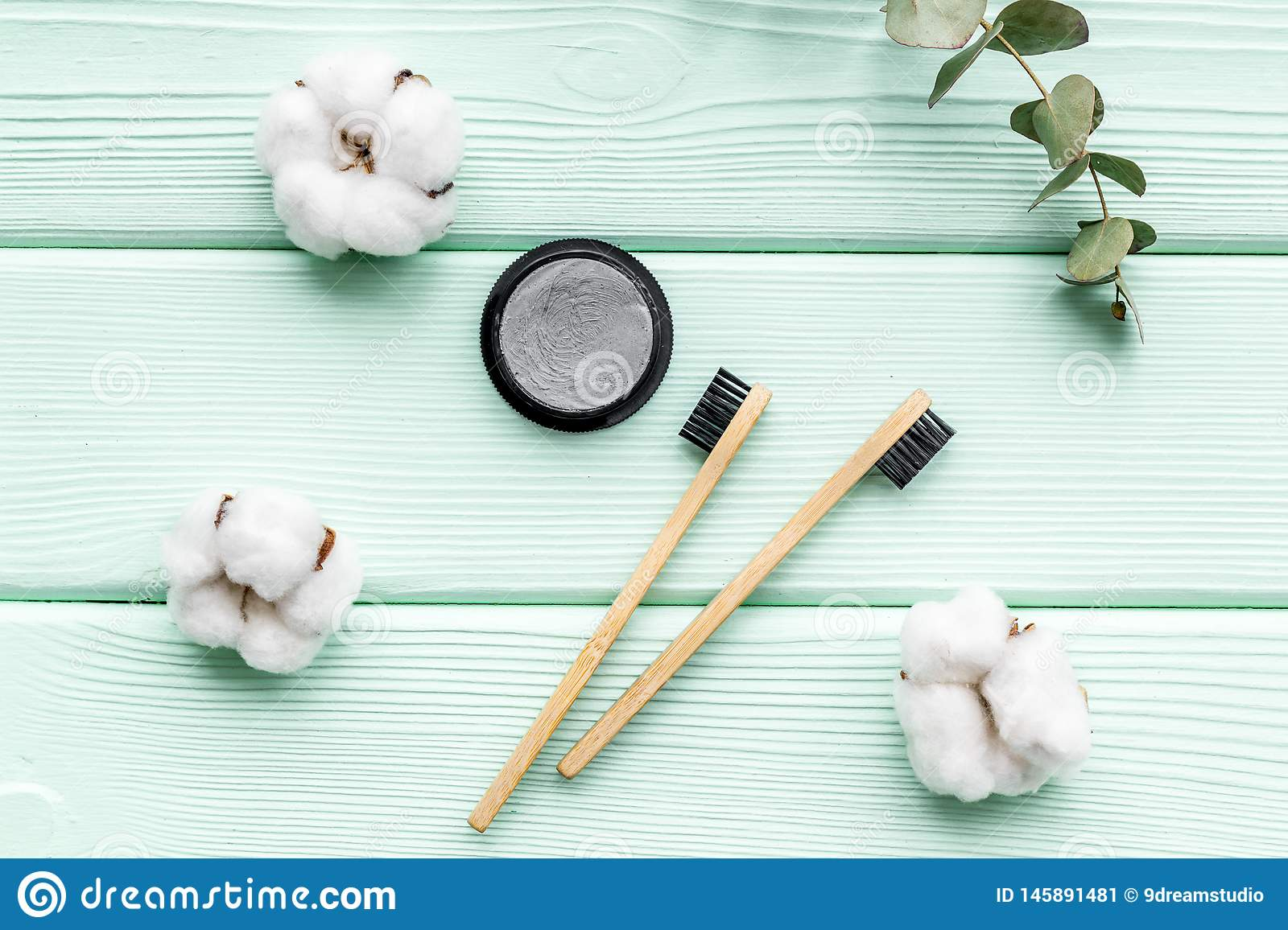 Bamboo dental cleaning brush and carbon toothpaste for zero waste lifestyle concept on mint green background top view. Bamboo dental cleaning brush and black stock image