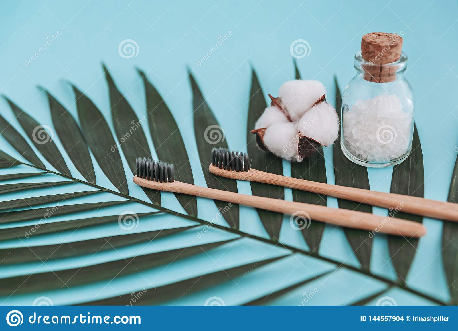 Bamboo toothbrushes, glass bottle with sea salt, cotton flower on palm leaf on blue background. Zero waste concept