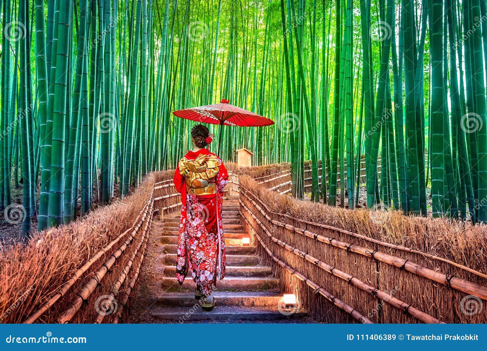 BambuForest Asian kvinna som bär den japanska traditionella kimonot på bambuskogen i Kyoto, Japan