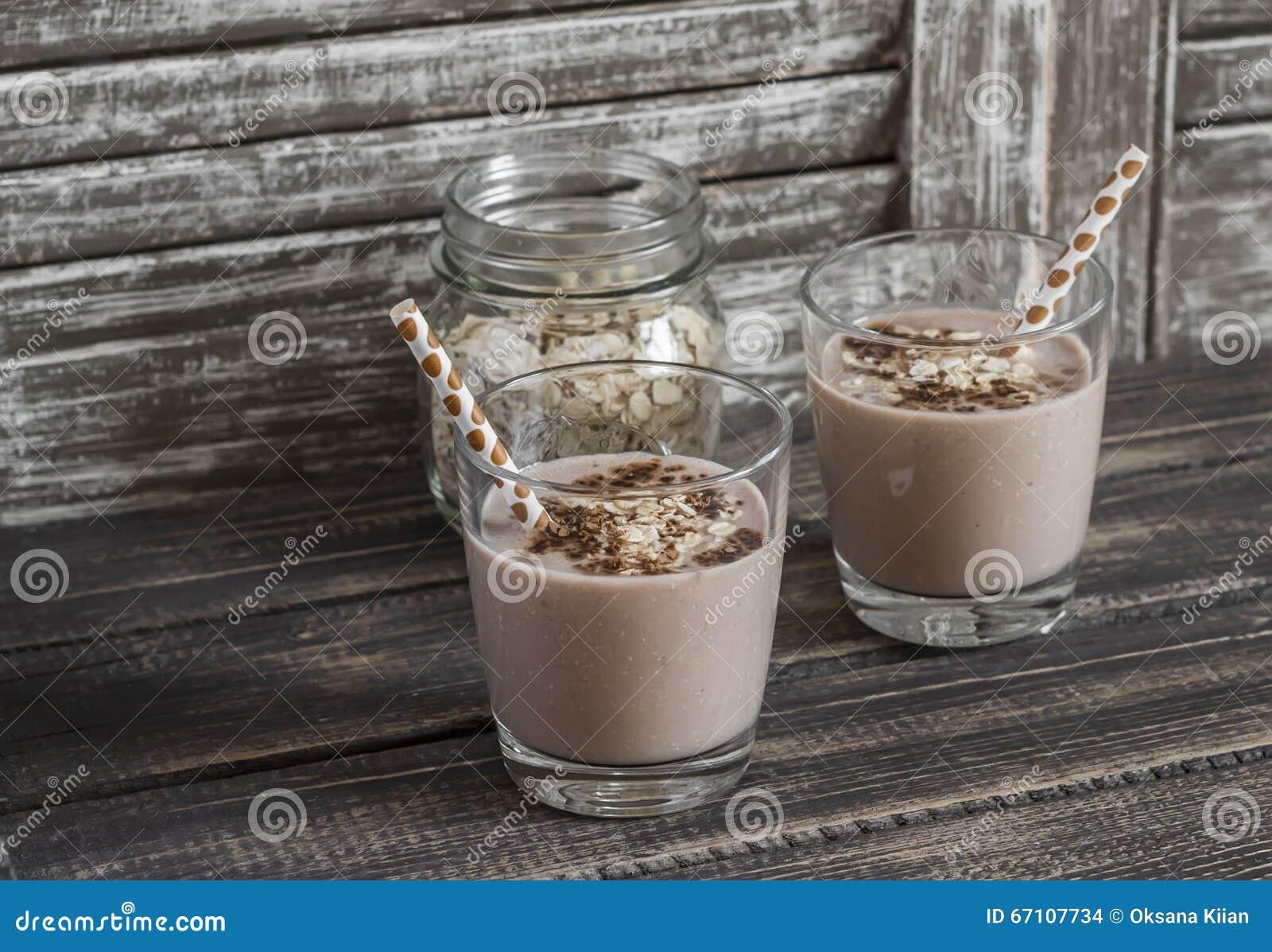 Banan-, havremjöl- och chokladsmoothie På en mörk lantlig träbakgrund Sund drink