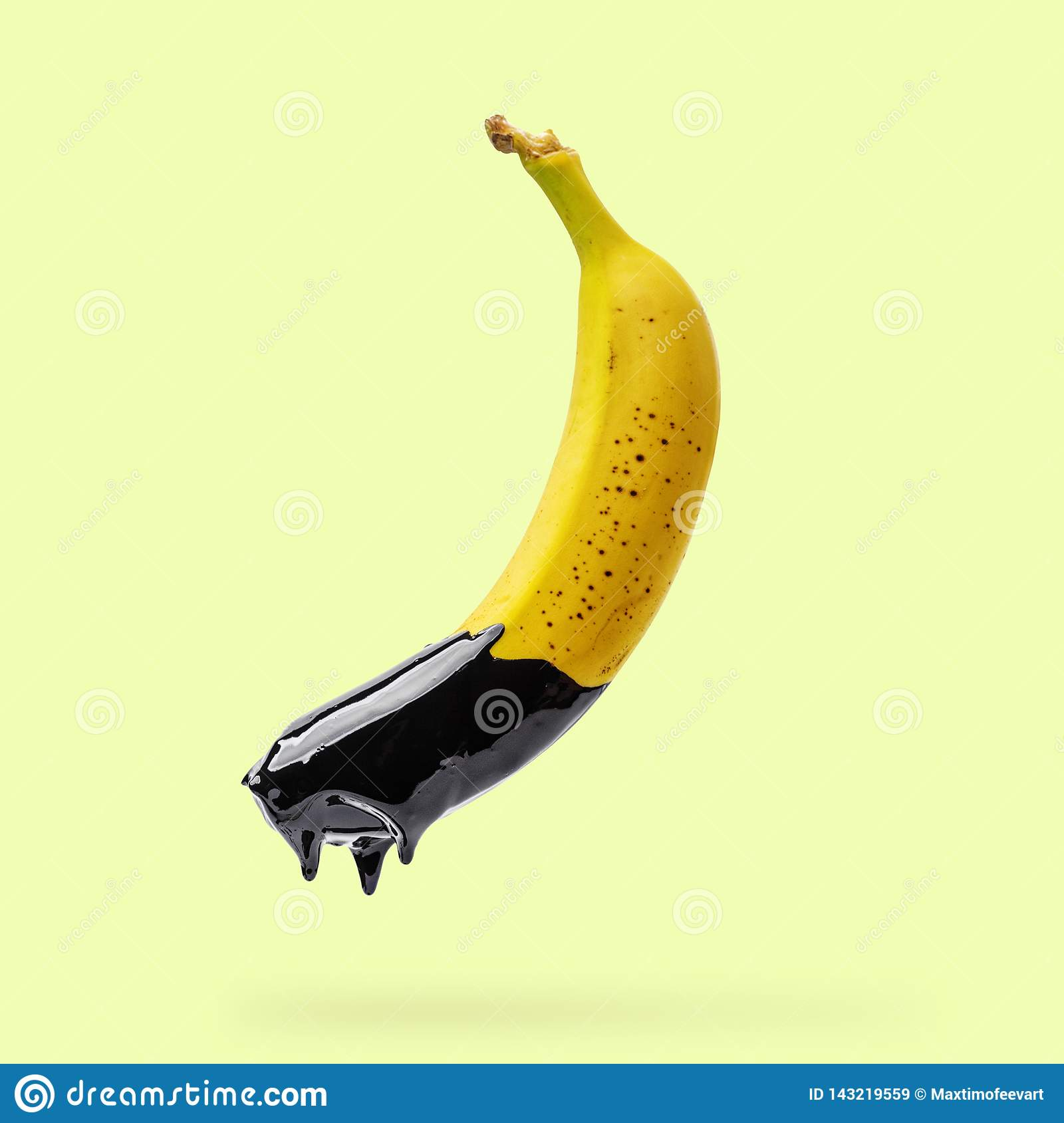 Banana with dripping black paint on yellow background. Creative food concept