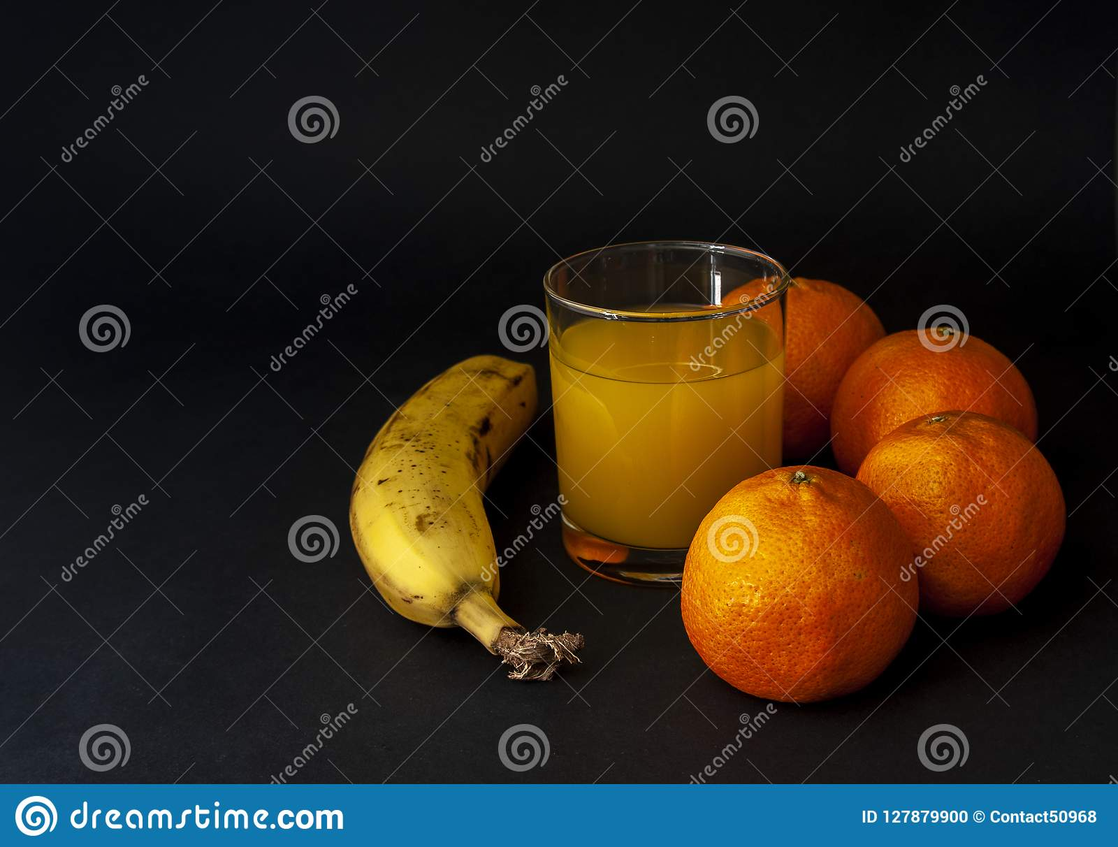 Banana and group of tangerines, mandarins with glass of juice dr