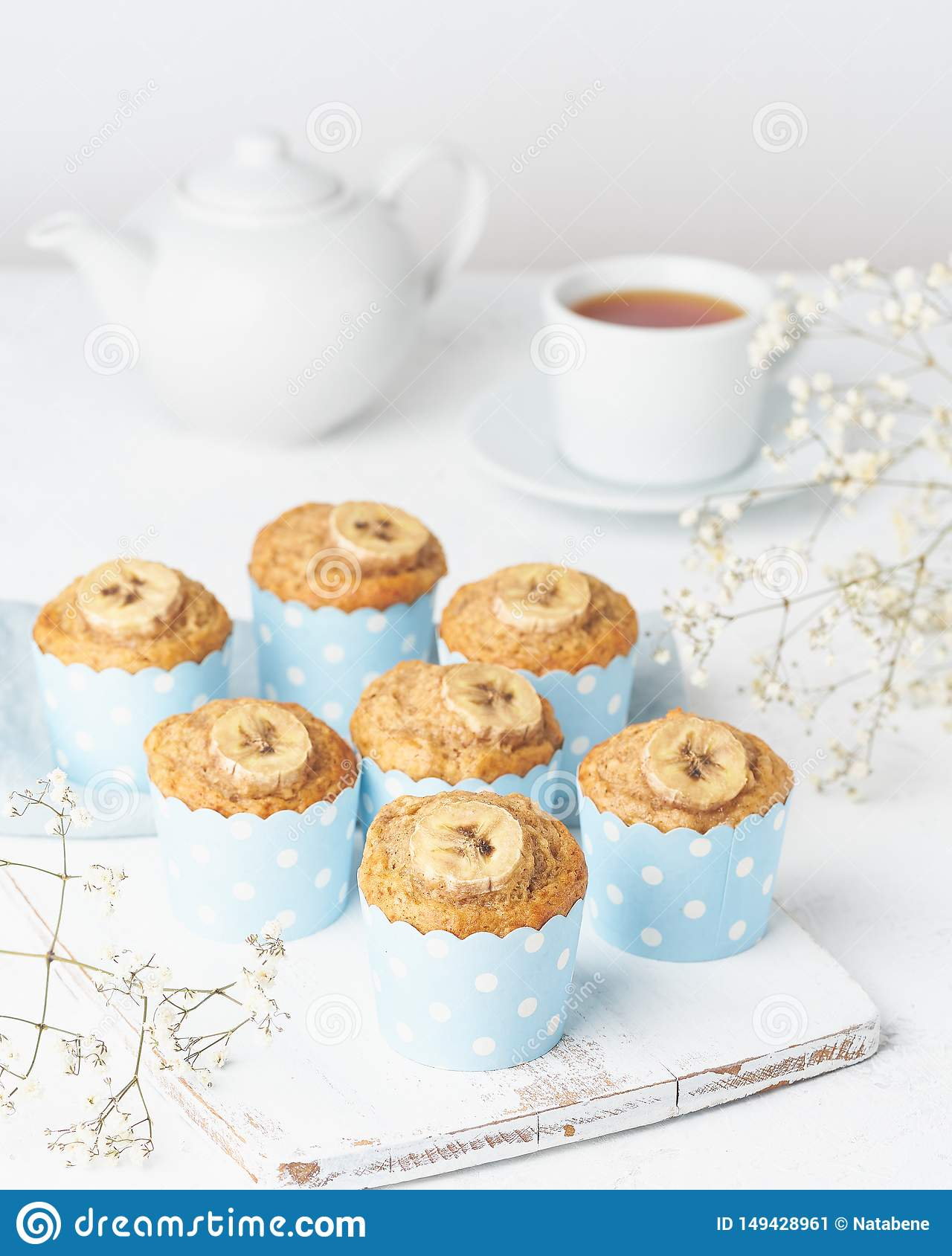 Banana muffin, cupcakes in blue cake cases paper, side view, vertical, white concrete table
