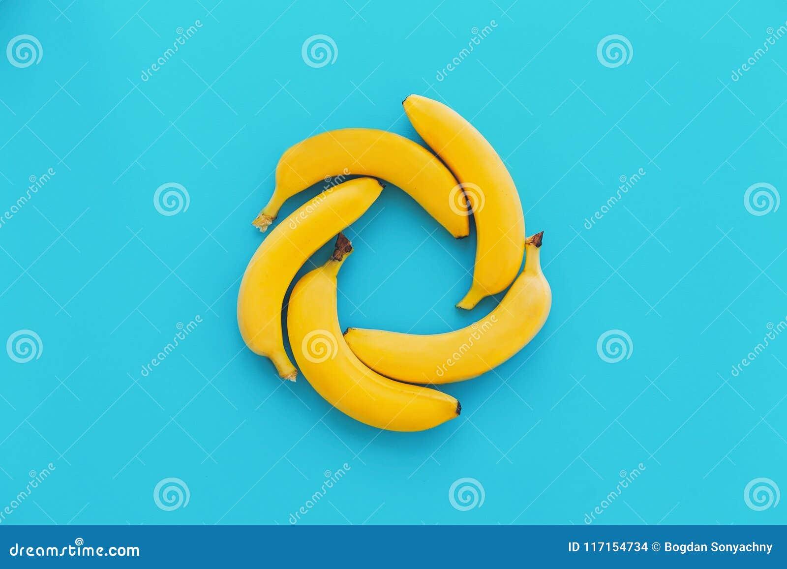 Bananas amarelas no círculo no fundo na moda do papel azul, liso