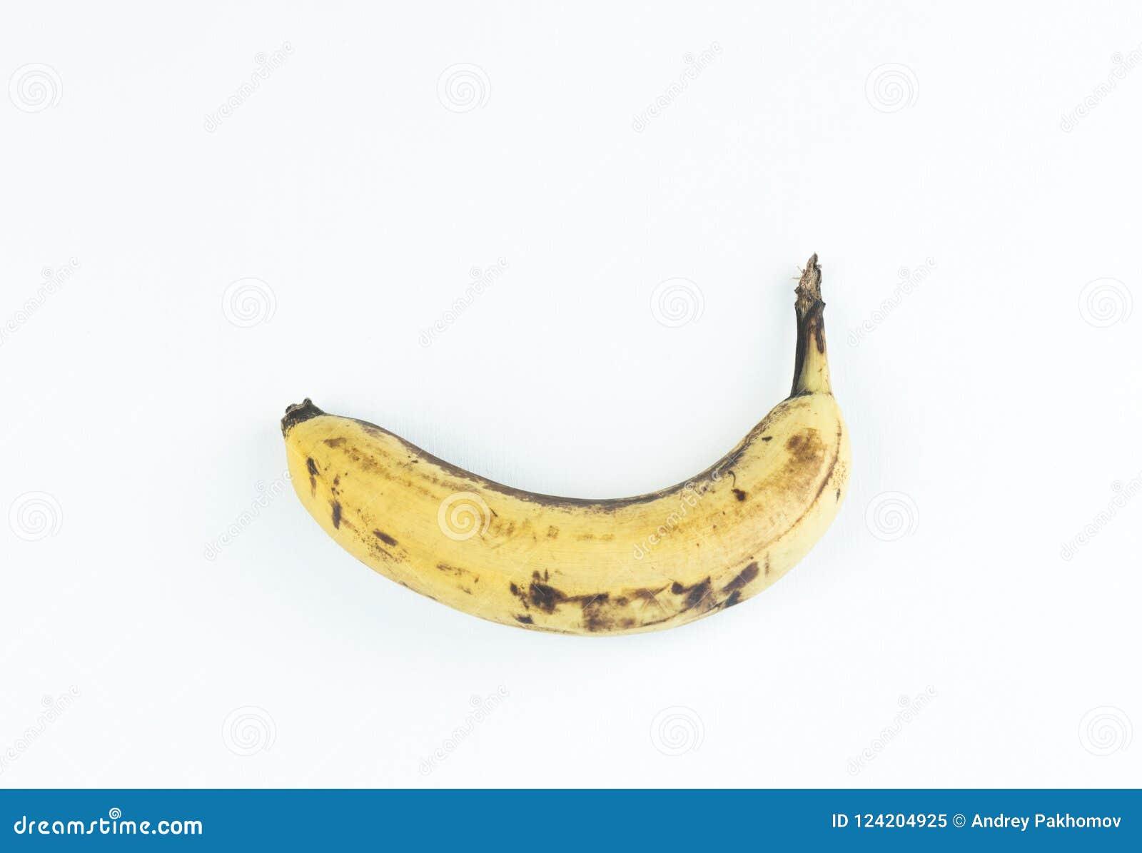 Banane gialle mature della frutta, banana matura con i punti scuri su un fondo bianco con il percorso di ritaglio