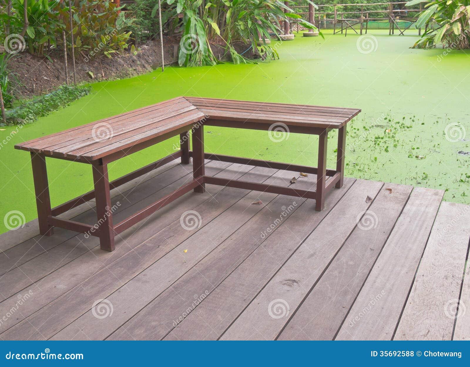 banc en bois angle droit sur la v randa pr s de l 39 tang vert de la lenticule photos libres de. Black Bedroom Furniture Sets. Home Design Ideas