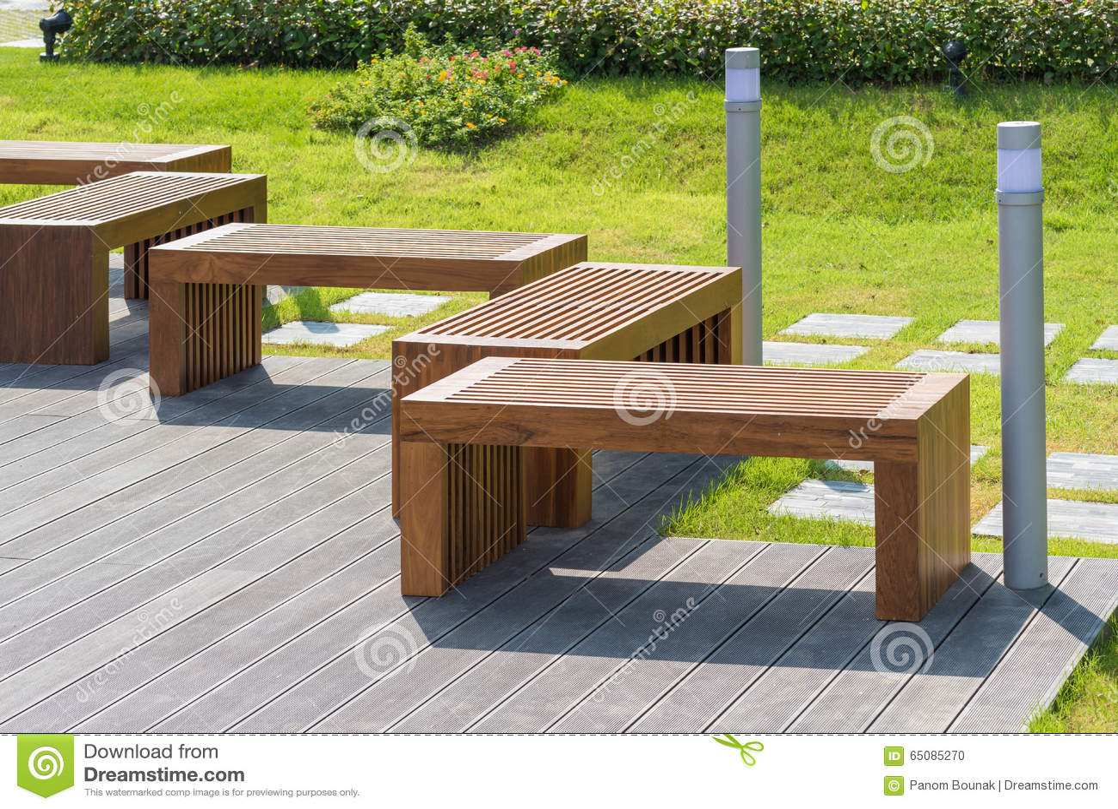 banc en bois dans le jardin avec le petit arbre vert à l'arrière