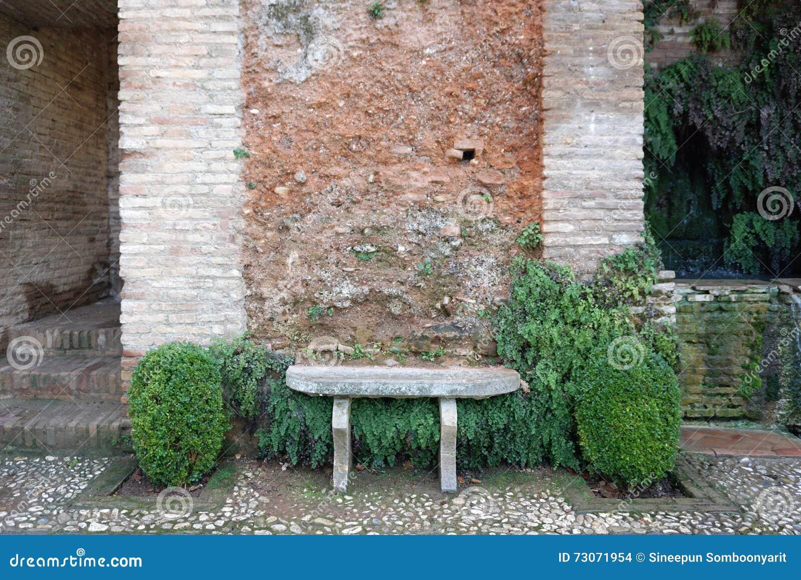 banc en pierre avec le mur de briques rustique photo stock - image