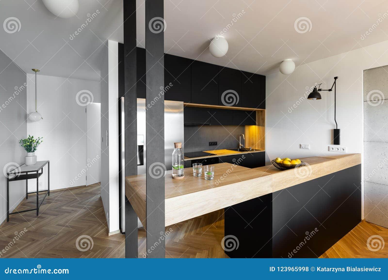 Bancada bege no interior preto e branco da cozinha de wi da casa