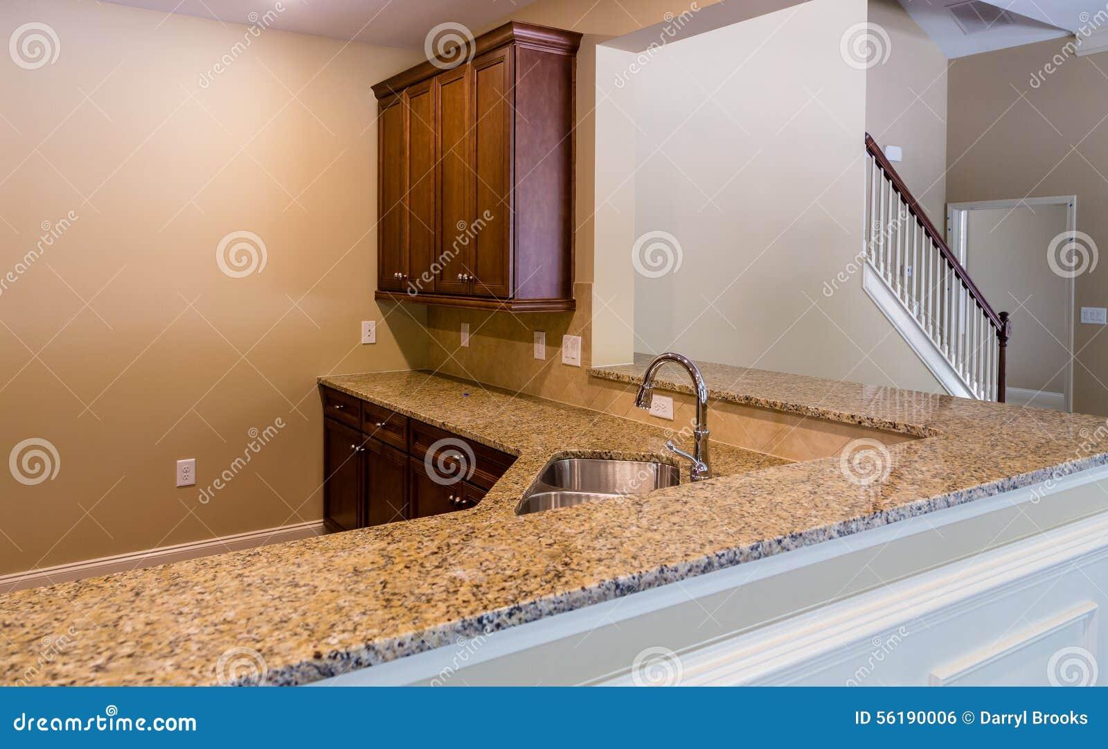 Bancadas do granito em uma cozinha agradável em uma casa nova. #39190A 1300 895