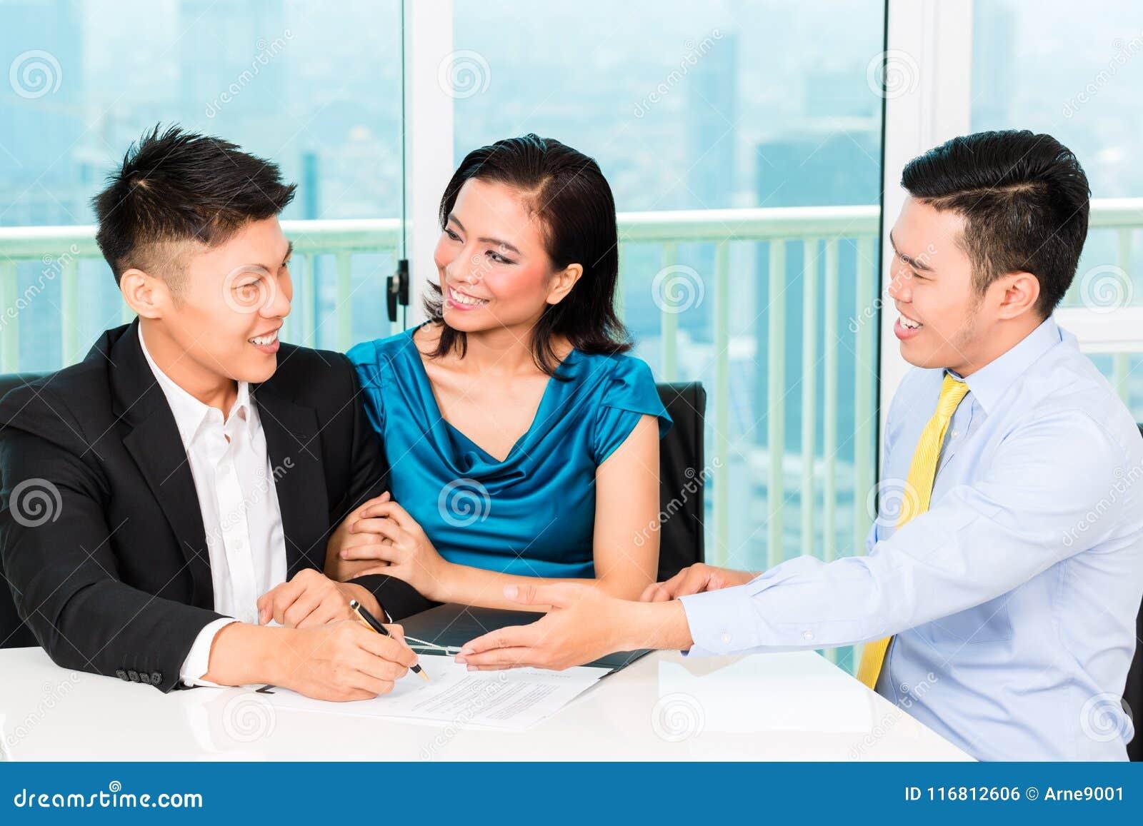 Banchiere asiatico che vende assicurazione alle coppie