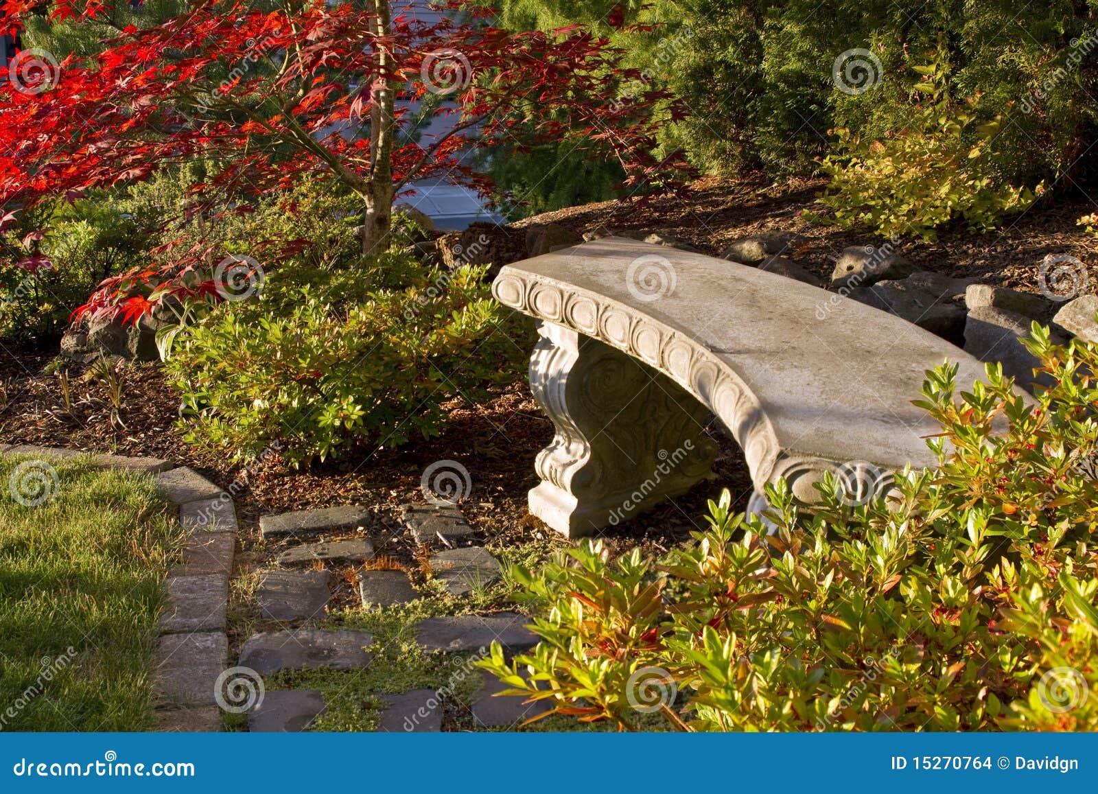 banco de concreto para jardim em jundiai : banco de concreto para jardim em jundiai:Banco concreto do jardim em Cobblestones com árvores e arbustos.
