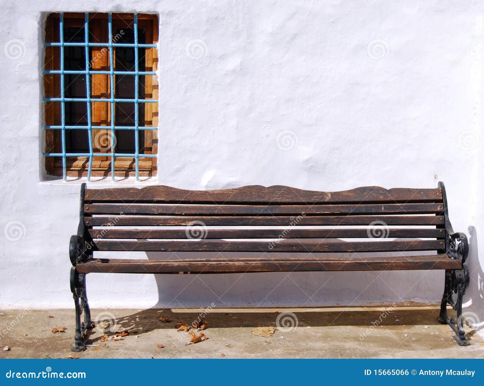 Um banco de madeira resistido velho de encontro a uma parede lavada  #267AA5 1300x1054