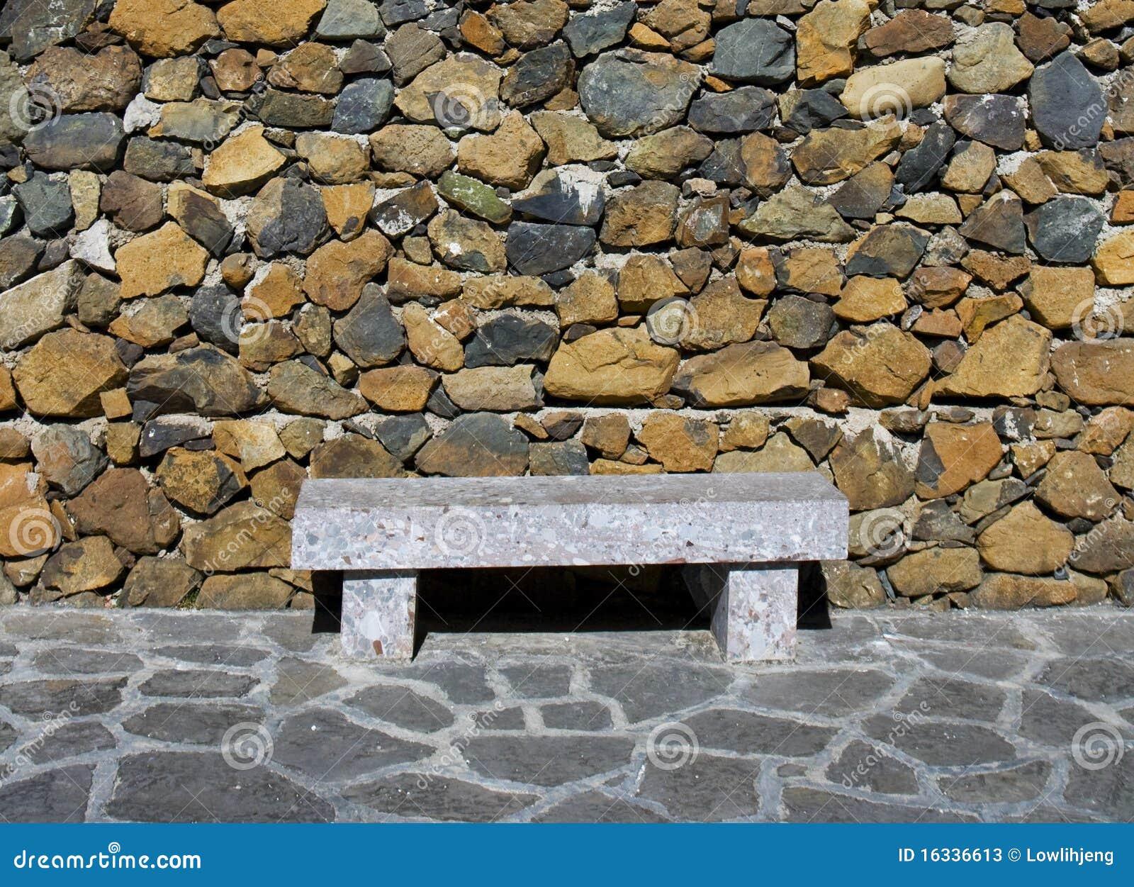 Banco de piedra contra la pared de piedra fotos de archivo for Banco de piedra para jardin