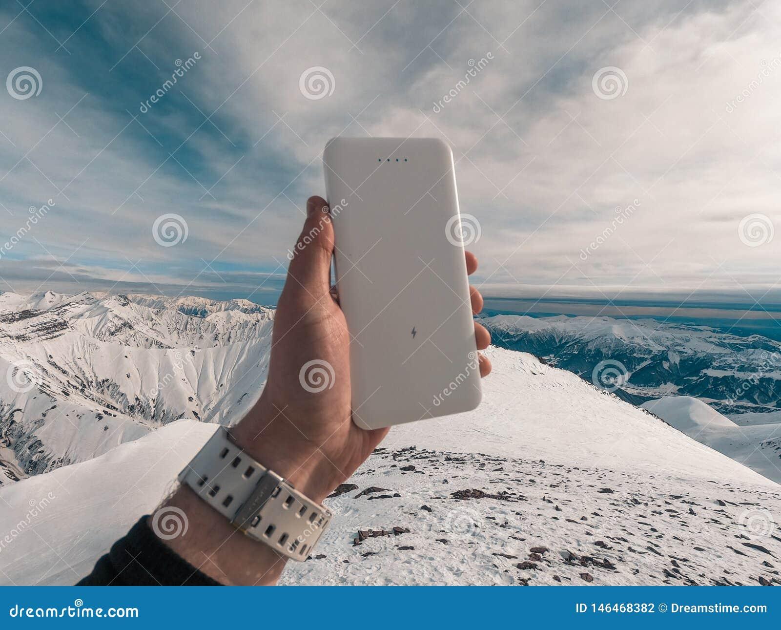 Banco del poder en manos Las cargas tur?sticas los dispositivos en naturaleza, contra el contexto de las monta?as de un invierno