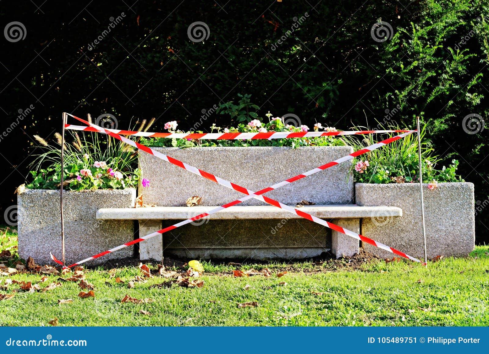 Banco severo con nastro adesivo bianco rosso di cautela in parco