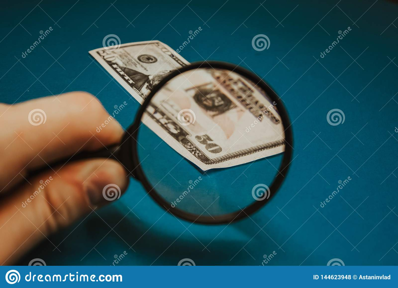 Banconota in dollari cinquanta sugli antecedenti blu tramite una lente d ingrandimento