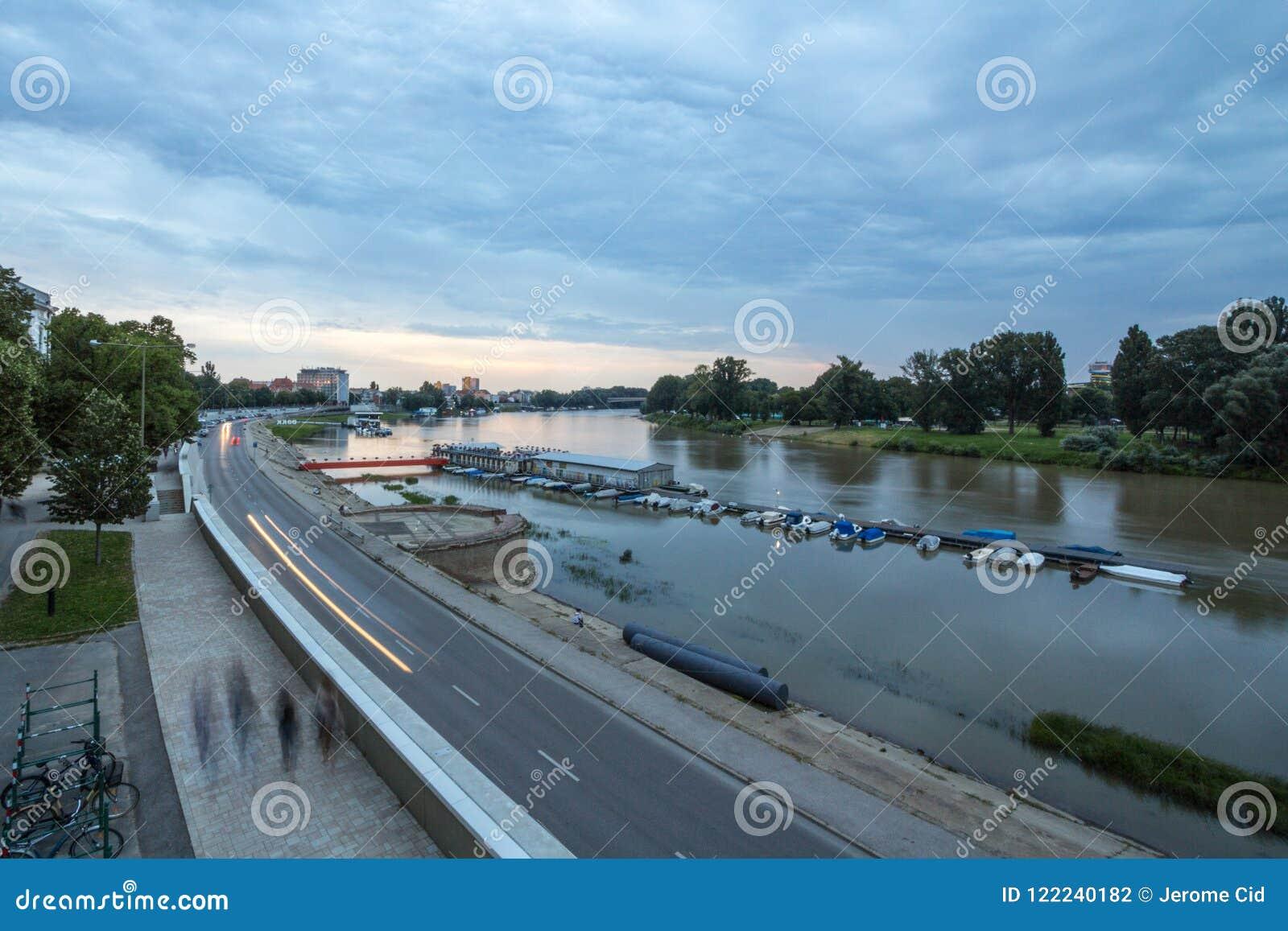 Bancos de rio de Tisza no centro da cidade de Szeged, visto na luz durante o por do sol durante uma tarde nebulosa do verão