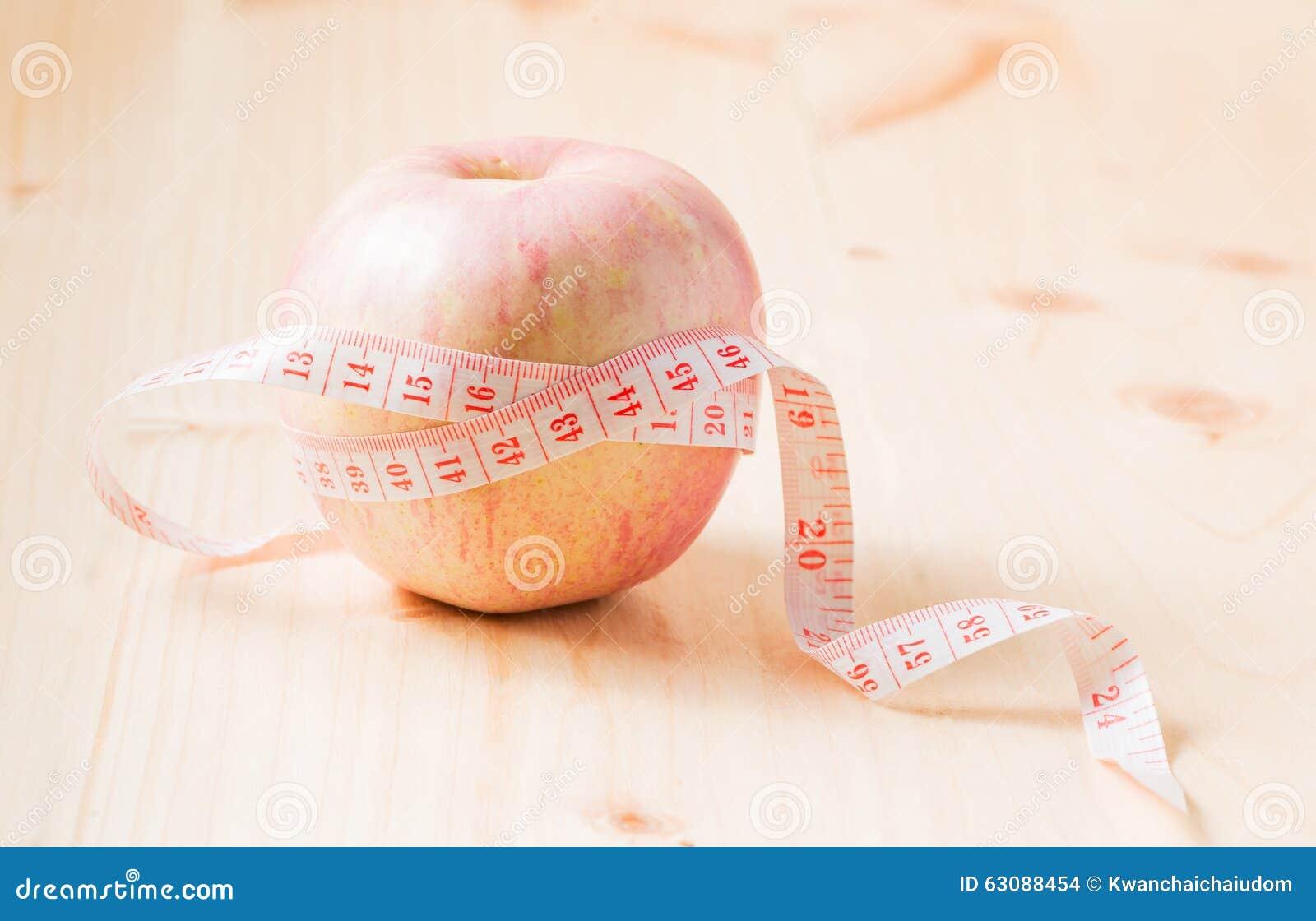 Download Bande De Mesure Enroulée Autour De La Pomme Comme Symbole De Régime, Sur Le Bois Photo stock - Image du poids, dieting: 63088454