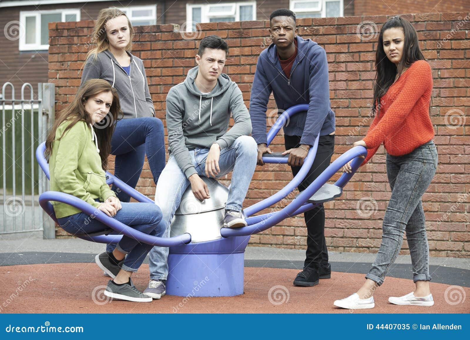 Bande des adolescents traînant chez le terrain de jeu des enfants